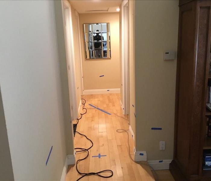 hallway with blue tape strips on wall and wood floors
