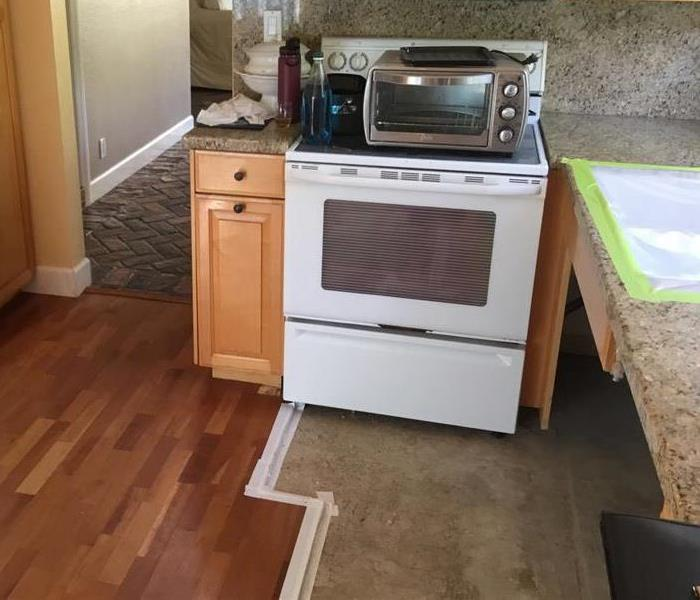 Oven pushed back to wall with tape on floor present