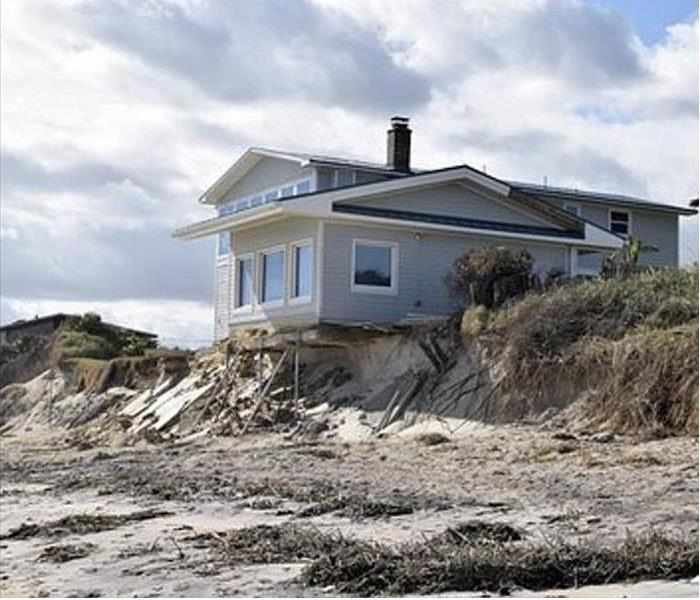 House on the beach with storm damage. Large area of sand.